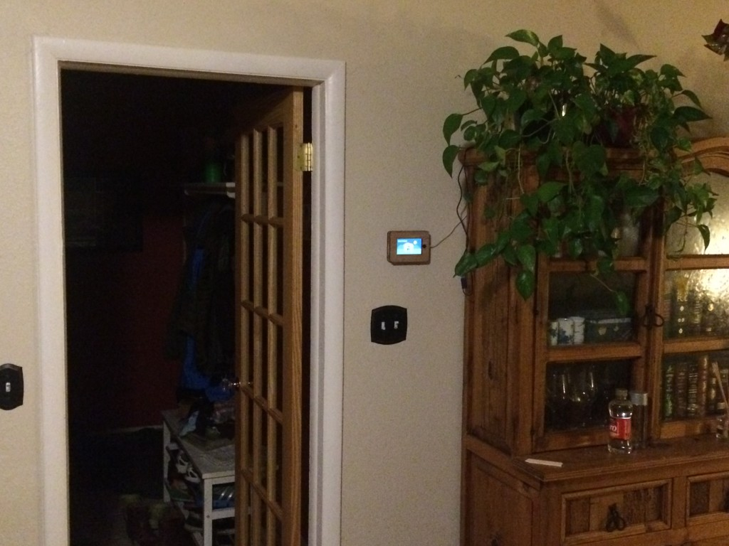 The iPhone 5 frame mounted next to the raspberry pi in our living room, and its USB power cable is plugged into the rpi.